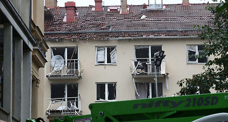 En bild på en vägg på ett hus med trasiga fönster