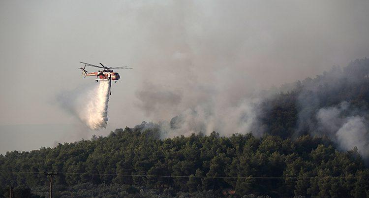 En helikopter flyger över en skog. Det är tjock rök i bakgrunden.