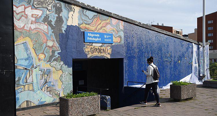 En mur till häften med graffitti och till hälften målad blå