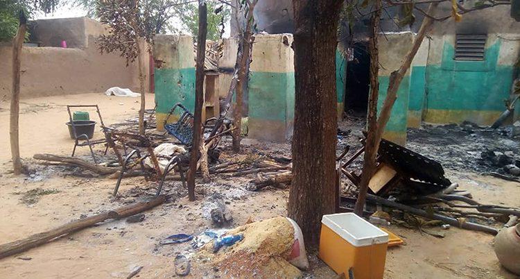 Ett förstört hus. Framför ligger brända och välta stolar och bord.