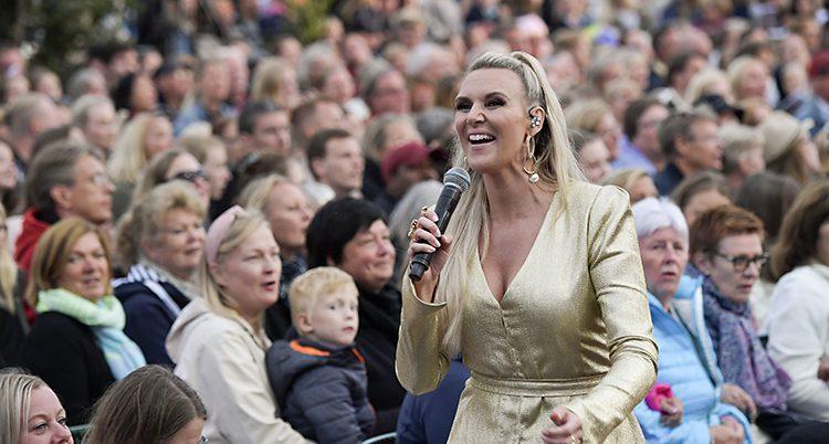 Sanna ler och sjunger. Masor av folk i bakgrunden.