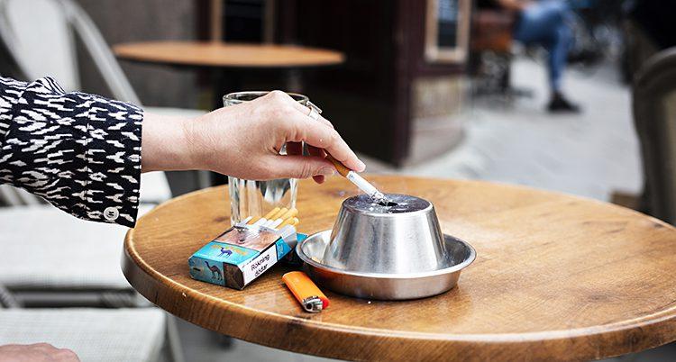 En hand med en cigarett och en askkopp