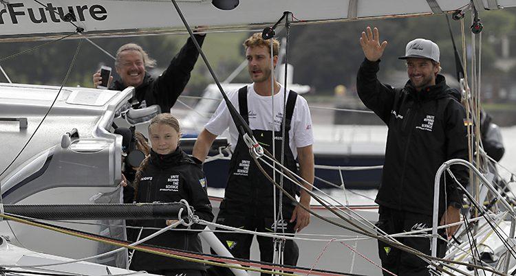 Greta och tre män på segelbåten. Greta ler, två av männen skrattar och vinkar.