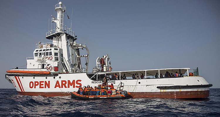 Båten Open Arms i Medelhavet. Vid sidan om båten finns en liten gummibåt med flyktingar.