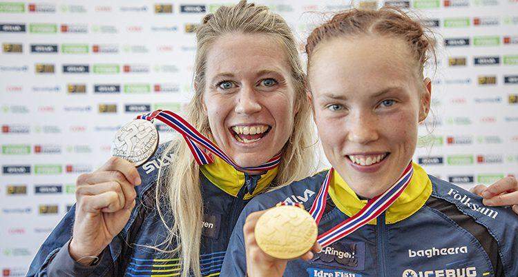 De båda står nära varandra, ler mot kameran och håller fram sina medaljer.