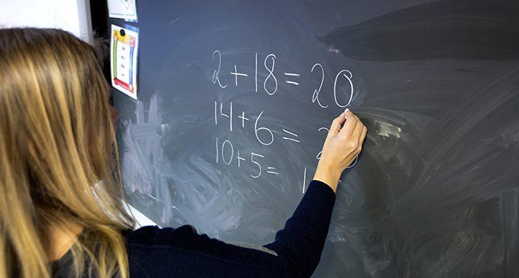 En person skriver med krita på en svart tavla.