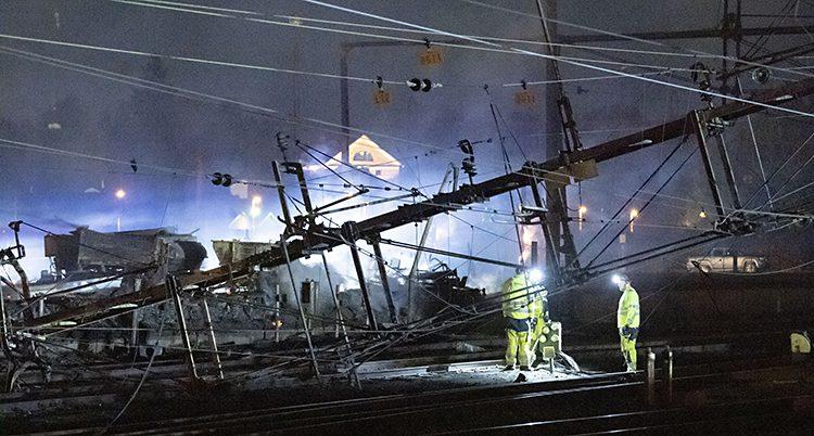 Bild tagen på natten. Stolåar och ledningar hänger på snedden. Folk i gula overaller arbetar med dem.