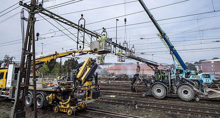 Flera maskiner står på spåren. Flera personer arbetar med ledningarna som går på stolpar uppe i luften.