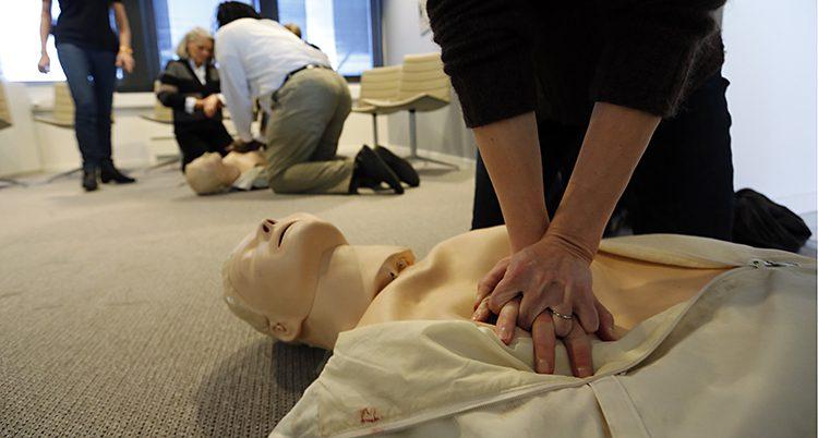 En person trycker sina två händer på varandra över en fullstor vit dockas bröst.