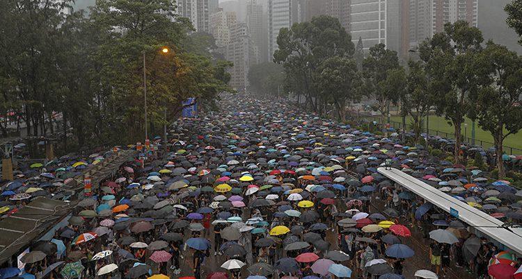 En gata täckt med paraplyer i olika färger. Mest svart men även gult, rött, vitt mfl.