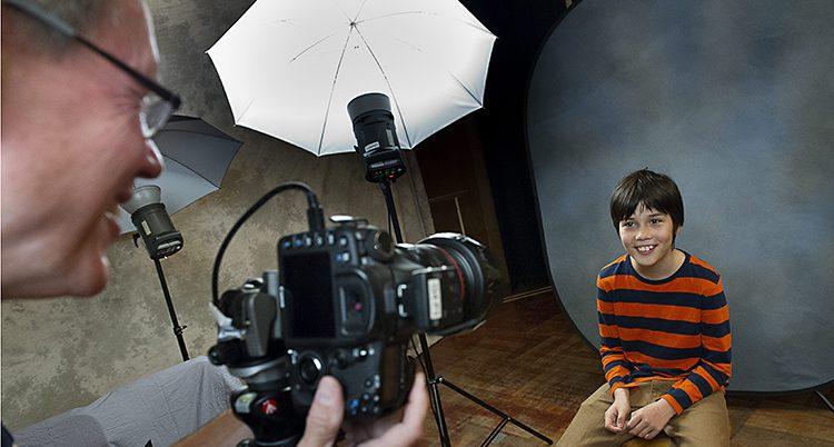 En elev sitter på en stol och blir fotograferad av en fotograf.