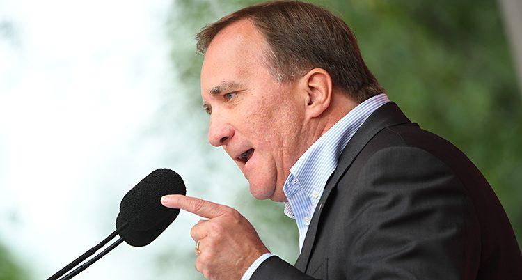 Stefan Löfven i profil framför en mikrofon. Han pekar och ser bestämd ut.