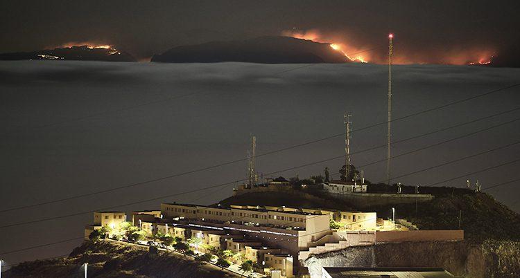 Hav i förgrunden. I bakgrunden två mörka kullar där det brinner på ryggen av kullarna. Bilden är tagen en mörk kväll.