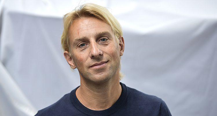 En närbild på läkaren och författaren Anders Hansen. Han har ljust hår och en mörkblå tröja på sig.