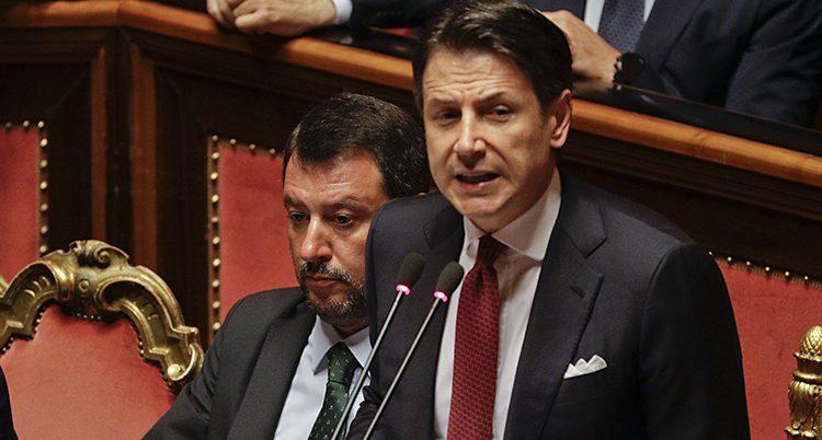 Ganska nära bild på båda männen. Conte ser bestämd ut när han pratar in i mikrofonen. Salvini tittar ner och ser dyster ut.