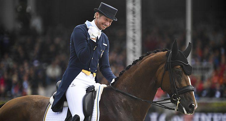 Patrik knyter näven och ler stort när han sitter på hästen.