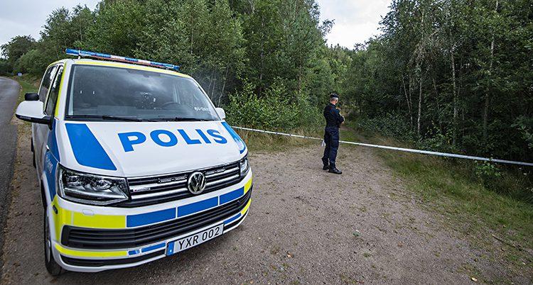 En polisbil och en polis står vid en vägkant. Där finns ett avspärrningsband och på andra sidan bandet är en skog.