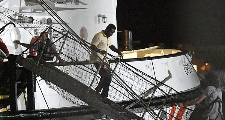 En man går nerför en liten bro som går mellan en båt och en kaj. Det är mörkt ute.