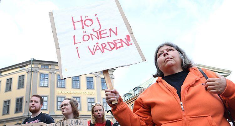 En sköterska med plaket där hon skrivit Höj lönen i vården.