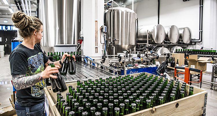 En kvinna plockar flaskor med öl in i en stor låda.