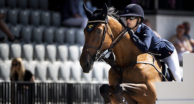 En näbild på hästen och Malin mitt i ett hopp. Hon lutar sig fram över halsen på hösten.