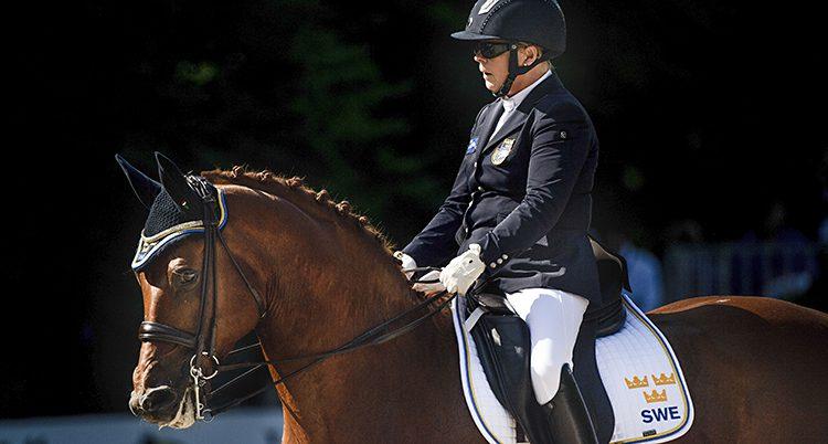 Louise sitter på sin häst som har en liten mössa på sig med tre kronor.