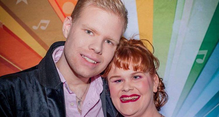 En blond man och en rödhårig kvinna ler och tittar in i kameran. De står mot en vägg i regnbågens alla färger.