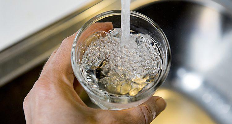 En hand håller i ett glas under en kran. Vatten rinner ner i glaset.