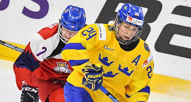 Närbild på Erika under en hockeymatch. Hon har en back bakomsig och verkar vara på väg att anfalla
