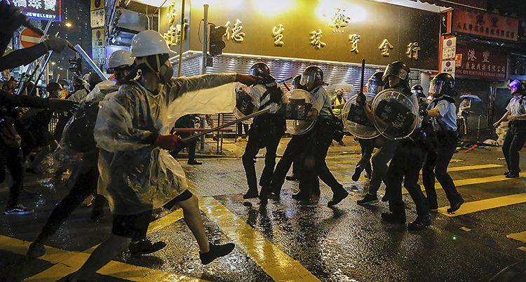 Människor med flaggor och hjälmar möter poliser med sköldar. Det är mörkt ute.