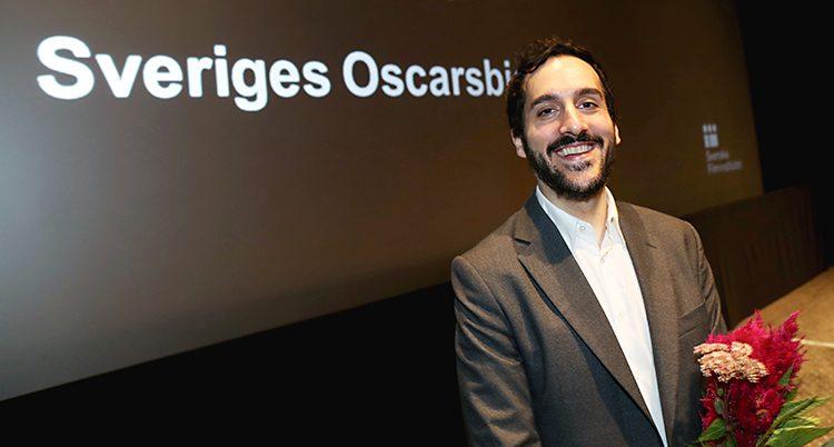 En glad regissör framför en vägg där det står Sveriges Oscarsbidrag.