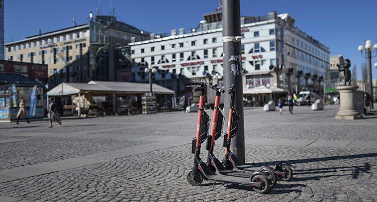 Tre sparkcyklar står vid en lyktstolpe på ett torg i Stockholm