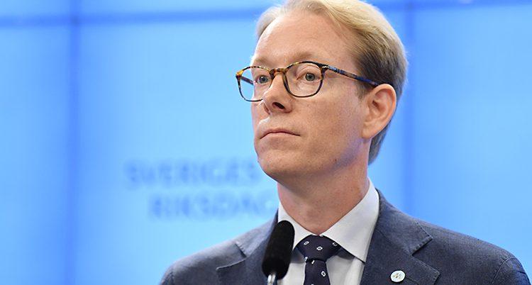 Tobias Billström har glasögon och kavaj och står framför en blå vägg i riksdagen