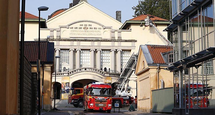 En brandbil står på en gata framför en stor vitt hus som är byggt i gammal stil.