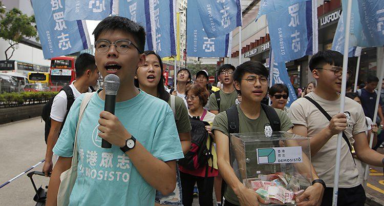Joshua Wong står framför många människor och talar i en mikrofon.