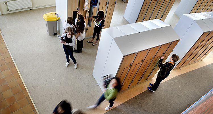 En bild från en skola. Den är tagen uppifrån. Nere ser man skåp och elever.