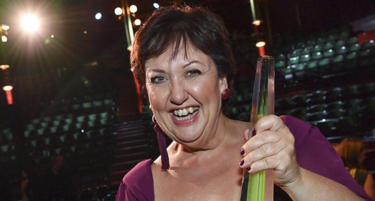 Babben Larsson i lila klänning skrattar och håller fram sitt pris mot kameran. En grön lång glasskulptur i en spettliknande form.