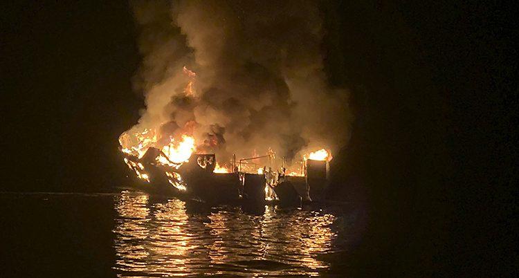Det kommer eld och rök från en båt som ligger på mörkt vatten.