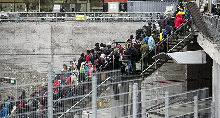 Ett foto av en trappa som går upp från ett tågspår. Trappan är full med människor. Det är sen höst så människor har mycket kläder på sig.