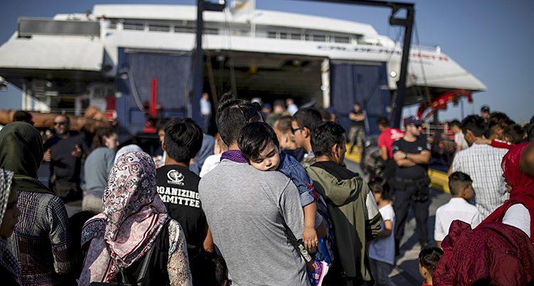 Flyktingar med barn på väg mot en vit färja
