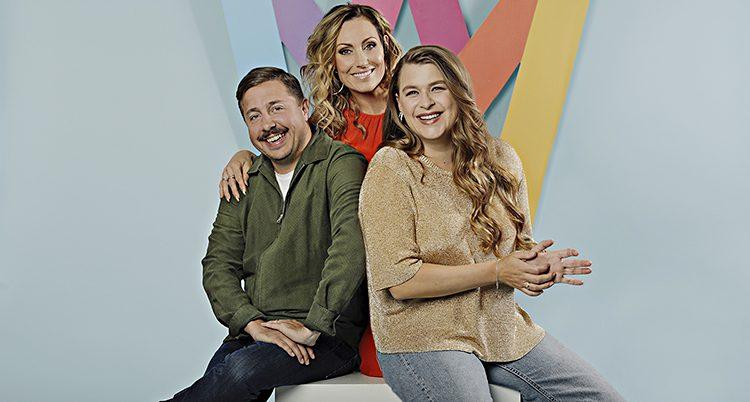 De tre programledarna sitter tillsammans. De ser glada ut.
