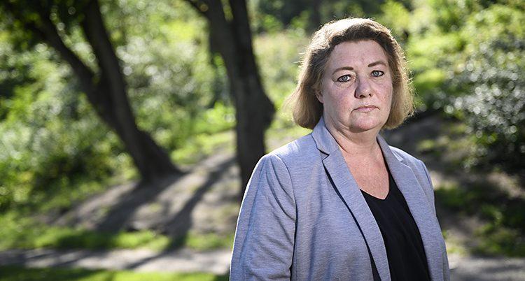 En bild tagen i halvfigur av en kvinna. Hon har en svart tröja och en lila kavaj på sig. Hon verkar stå i en park och solen lyser upp buskarna i bakgrunden. Kvinnan heter Katarina Söderberg.