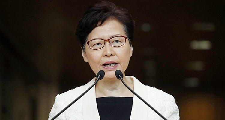 Hongkongs ledare Carrie Lam pratar med journalister. Hon pratar in i två mikrofoner. Hon har glasögon på sig, en svart tröja och en vit kavaj.