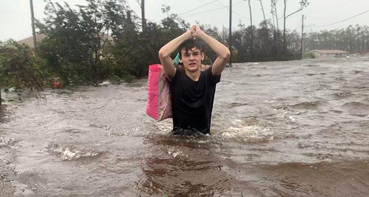 En ung man bär på en kasse medan han går genom brunt vatten