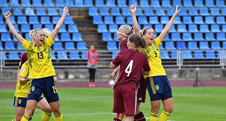 Två svenska spelare lyfter armarna i luften och jublar efter ett mål. De har gula tröjor och blå shorts. Några lettiska spelare syns också i bilden. De har röda dräkter. Läktaren i bakgrunden har blå säten.