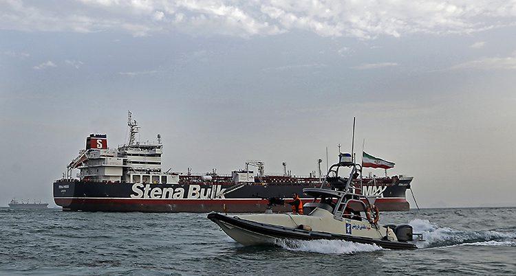 En mindre båt med militärer och iranska flaggor åker runt en stor båt som det står Stena Bulk på.