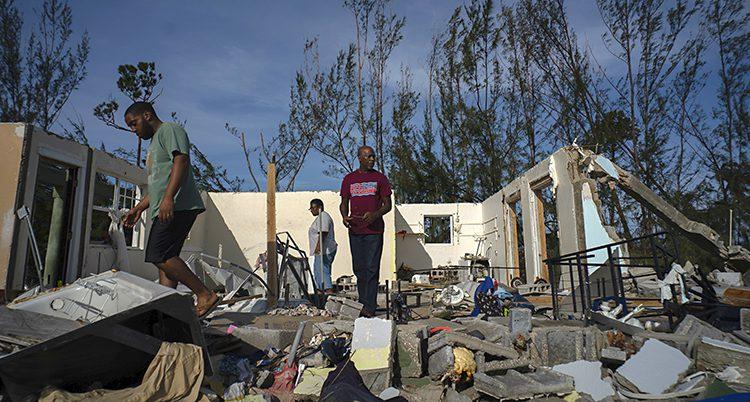 Tre människor går omkring i ett hus utan tak. En vägg är borta och allt i huset är förstört.