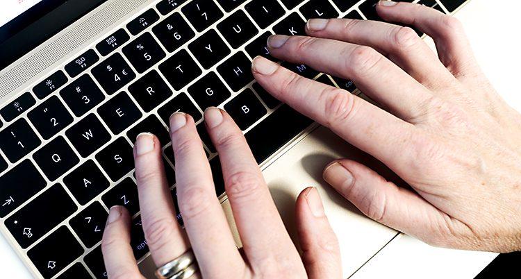 Två händer på ett tangentbord.