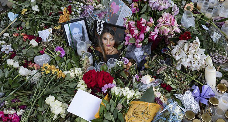 Blommor, fotografier och brev på platsen där en kvinna blev skjuten till döds.