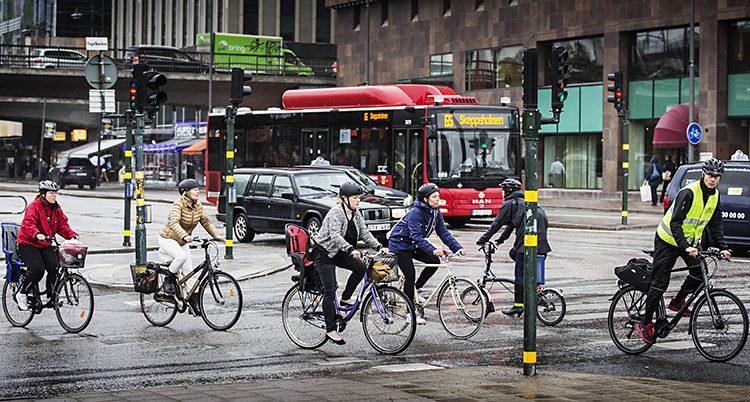 Flera personer cyklar i stadstrafik. En röd buss syns i bakgrunden.